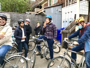 a number of people stand on bikes in an alcove between buildings, eating ice cream and laughing